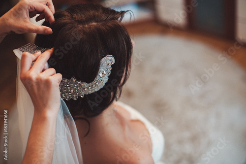 Fotografia The bride is wearing a veil. Beautiful long veil of white color