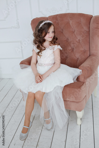 fa9911fa69c32 Beautiful little girl with curls and white Quinceanera dresses with a train  lying in a pink seat and fun dangles her legs