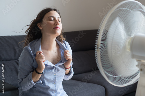 Fotografía  Young woman refreshing in front of cooling fan