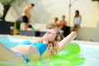 beautiful young woman lying on a pool mattress in the swimming pool of holiday resort during summer vacation