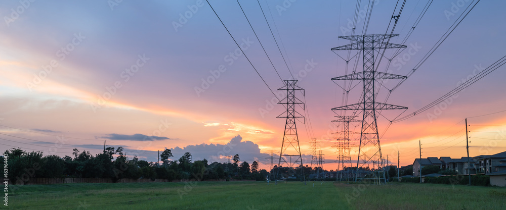 Fototapeta Group silhouette of transmission towers (power tower, electricity pylon, steel lattice tower) at twilight in US. Texture high voltage pillar, overhead power line, industrial background. Panorama style