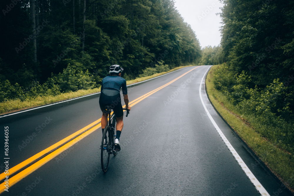 Fototapeta Selective focus shot of professional road cyclist riding down wet and windy mountain road in forest, on aero road bike from carbon