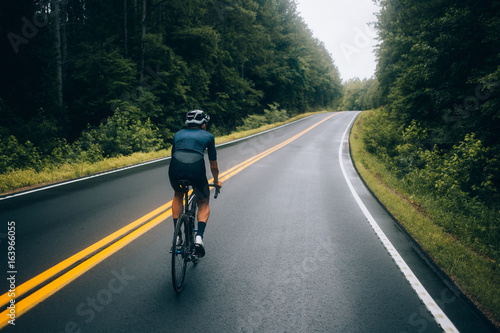 Cuadros en Lienzo  Selective focus shot of professional road cyclist riding down wet and windy moun