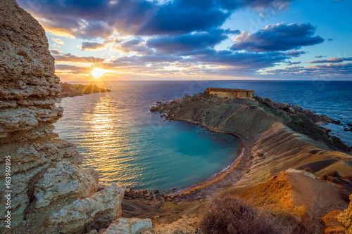 Foto op Aluminium Diepbruine Mgarr, Malta - Panorama of Gnejna bay, the most beautiful beach in Malta at sunset with beautiful colorful sky and golden rocks taken from Ta Lippija
