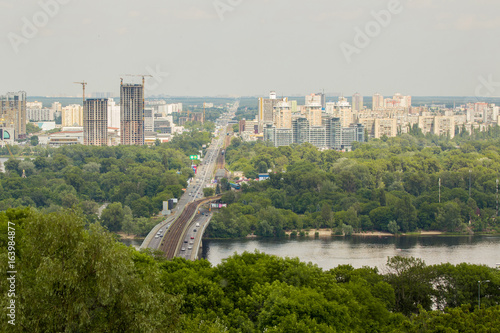 Foto  Panoramic landscape of modern developing metropolis with river, bridge, subway,