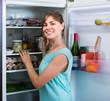 adult girl arranging space of fridge shelves indoors