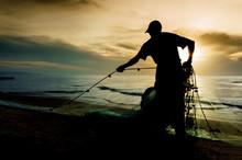 Silhouette Fisherman Working On Beach