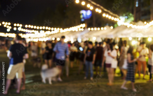 Abstract blurred background of people shopping at night festival