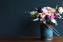 Various Fresh Flowers Arrangement In Metalic Vase On Wooden Table