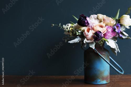 Fotografía Various fresh flowers arrangement in metalic vase on wooden table