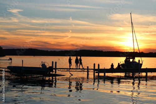 Plakat Letni zachód słońca nad jeziorem. Krajobraz z złotym zmierzchem i sylwetkami ludzie cieszy się pięknego wieczór na jeziornym Mendota molu w mieście Madison, Wisconsin, usa.