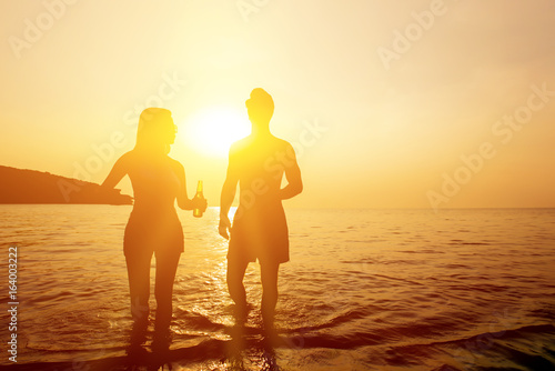 Fotografía Silhouette of couple walking in seawater at the beach in twilight sunset