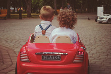 Children Boy And Girl Ride In A Children's Car
