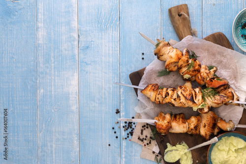 Fotografía  Chicken breast skewers with avocado sauce on blue wooden table