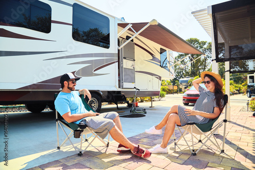 Foto op Canvas Kamperen Young couple sits near camping trailer,smiling.Men talks on mobile phone and uses electronic device, woman relax on chair near car and palms.Family spending time together on vacation in rv park