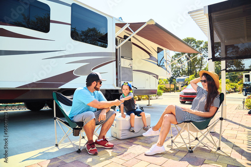 Foto op Canvas Kamperen Mother, father, son sittsng on chairs near camping trailer