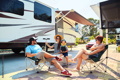 Spoed Foto op Canvas Kamperen Mother,father,son and grandmother sitting near camping trailer,smiling.Woman,men,kid relaxing on chairs near car.Family spending time together on vacation near sea or ocean in modern rv park