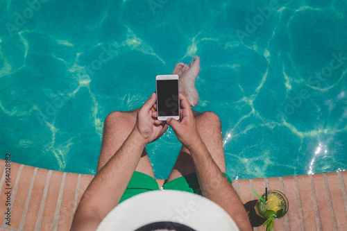 Poster Lieu connus d Asie Tourist sitting on edge of swimming pool and using blank screen smartphone