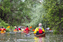 Group Of People (friends) Kayaking In Wild River Among Thickets Of Plants On Biosphere Reserve In Spring