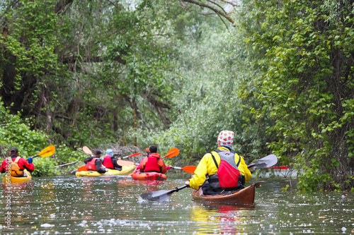 Group of people (friends) kayaking in wild river among thickets of plants on bio Tablou Canvas