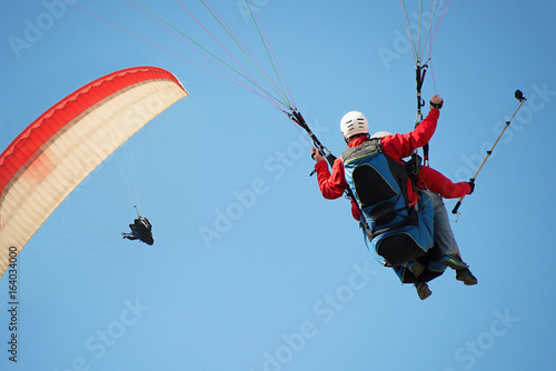 Foto op Canvas Luchtsport Two paraglider tandem fly against the blue sky,tandem paragliding guided by a pilot