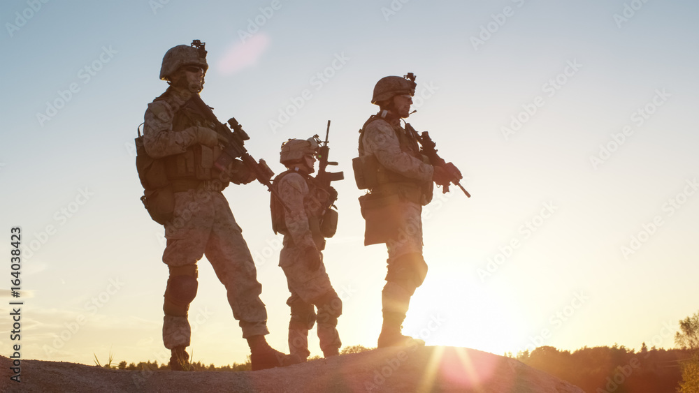 Fototapety, obrazy: Squad of Three Fully Equipped and Armed Soldiers Standing on Hill in Desert Environment in Sunset Light.