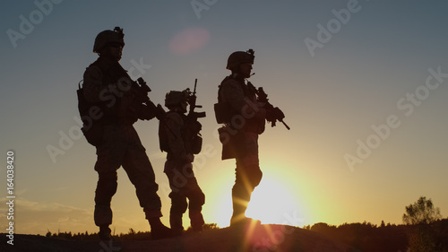 Squad of Three Fully Equipped and Armed Soldiers Standing on Hill in Desert Environment in Sunset Light Wallpaper Mural