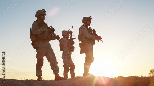 Photo Squad of Three Fully Equipped and Armed Soldiers Standing on Hill in Desert Environment in Sunset Light