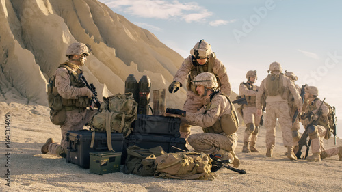 Fotografie, Tablou Soldiers are Using Laptop Computer for Surveillance During Military Operation in the Desert