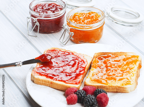 Fotografía  Tasty toast breakfast with strawberry and peach jam along with blackberries and raspberries on wooden table