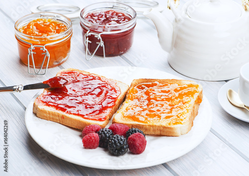 Fotografía  Tasty toast breakfast with strawberry and peach jam along with blackberries and raspberries