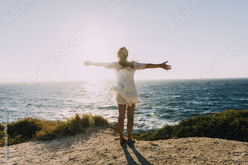 Greece, Cyclades, Naxos, woman with raised arms standing at the sea at sunset