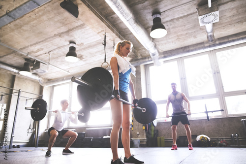 Young woman with training partners lifting barbell in gym