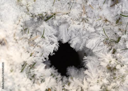 Fotografie, Obraz  Schneekristalle, Eiskristalle in winterlicher Landschaft um ein Erdloch