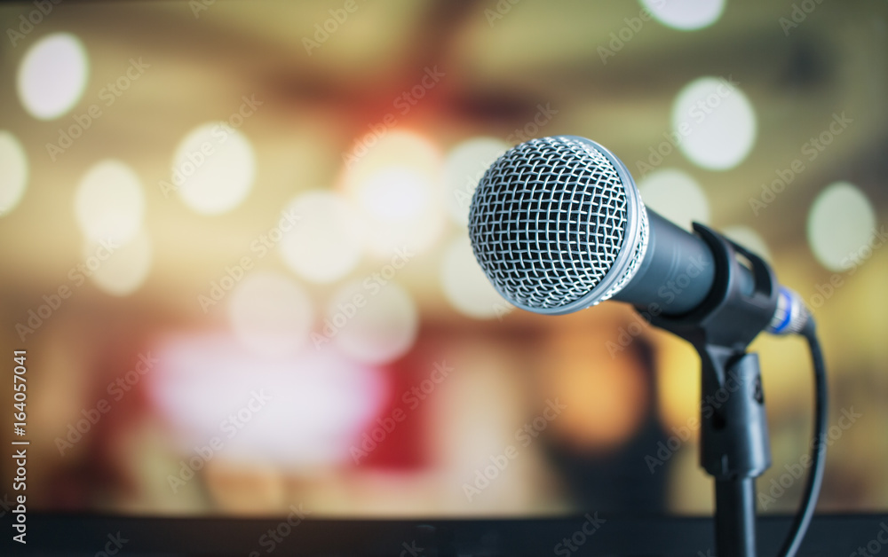 Fototapeta Microphone on abstract blurred of speech in seminar room or speaking conference hall light background