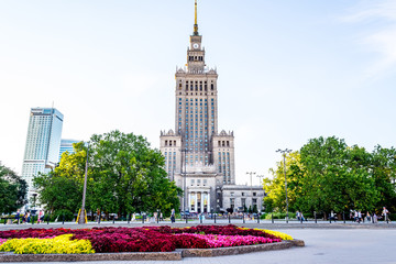 Palace of culture and science in Warsaw on sunny day with blue sky and green trees.