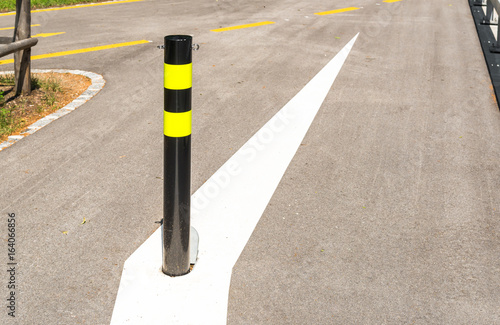 Black and yellow steel bollard on the road Canvas Print