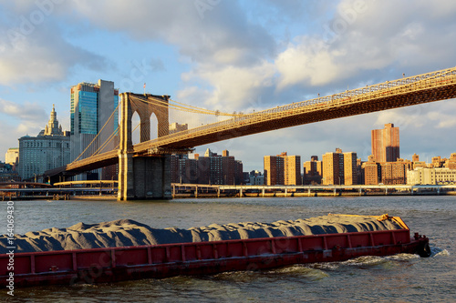 The barge floats along the Hudson River in the background of the Brooklyn Bridge