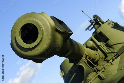 Plakat Działo baryłka potężny zielony zbiornik z niebieskim niebem na tle, nowożytna wojsko artyleria, przemysł wojskowy, selekcyjna ostrość