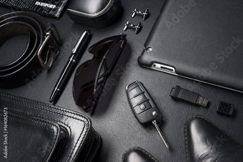 Fototapeta Man accessories in business style, gadgets, clothes, shoes, jewelry, and other luxury businessman objects on leather black background, fashion industry, selective focus obraz