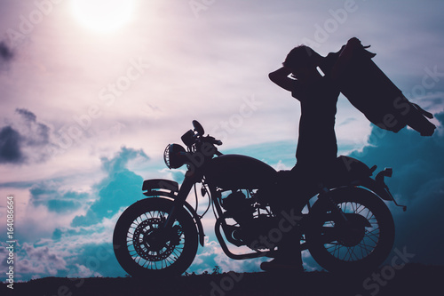 Photo Silhouette of biker man with his motorbike beside the natural lake and beautiful, enjoying freedom and active lifestyle, having fun on a bikers tour