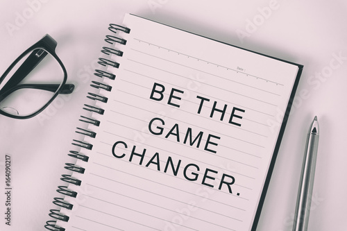 Inspirational quote - be the game changer: written on a note pad with eyeglasses and pen Wallpaper Mural