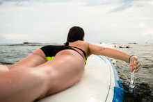 Female Surfer Paddling On Surfboard To The Open Sea