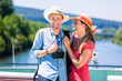 Happy couple on river cruise in summer wearing sun hats
