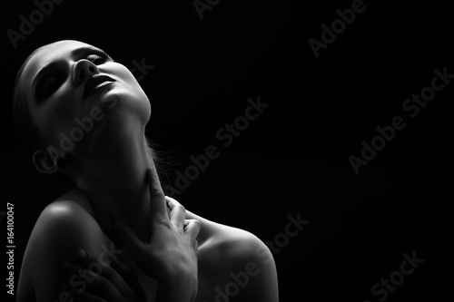 Photo  Black and white shot of woman posing sensually holding head up on black backgrou