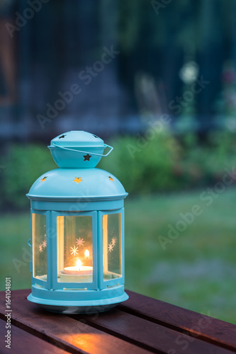 Photo  Scented candle in a pretty lantern with outdoor green background