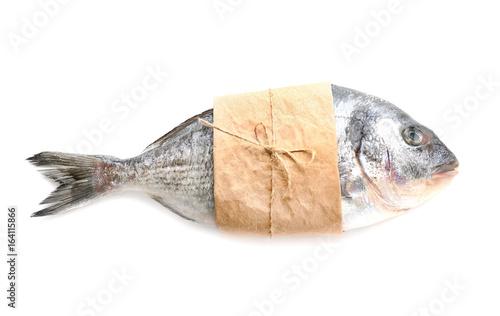 Fotografía  Fresh dorado fish wrapped in paper on white background