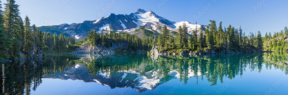Fototapety, obrazy: Volcanic mountain in morning light reflected in calm waters of lake.