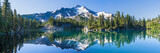 Fototapeta Natura - Volcanic mountain in morning light reflected in calm waters of lake.