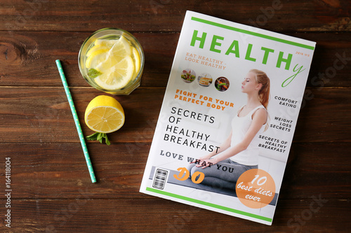 Glass of fresh lemonade and magazine on wooden background